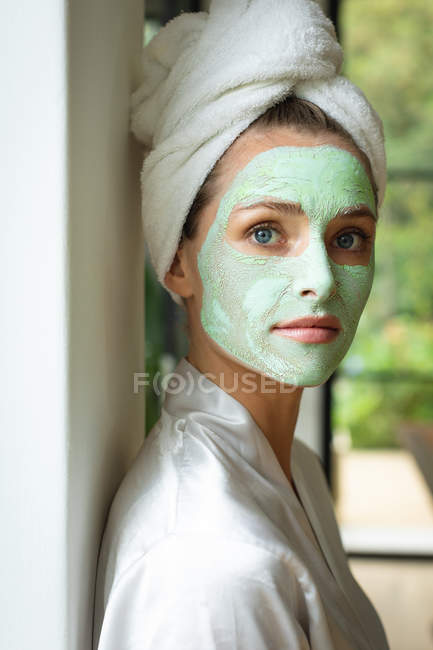 Porträt einer Frau mit Gesichtsmaske, die zu Hause in die Kamera schaut — Stockfoto