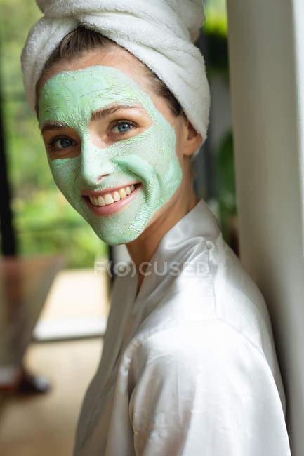Retrato de mulher na máscara facial olhando para a câmera em casa — Fotografia de Stock