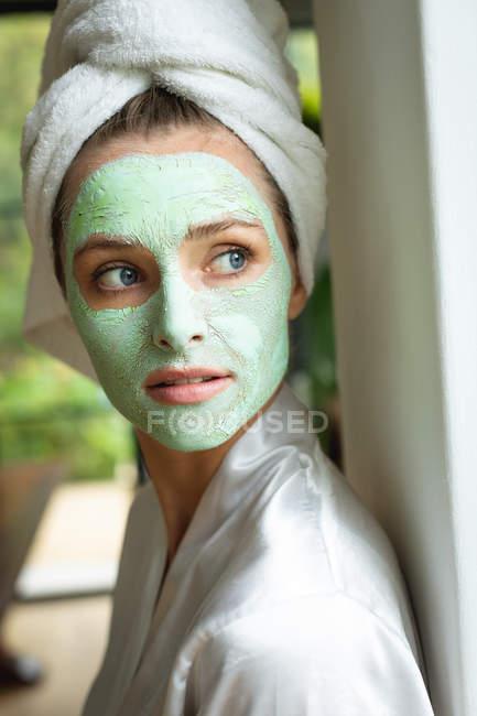 Seitenansicht einer Frau mit Gesichtsmaske, die zu Hause in die Kamera schaut — Stockfoto