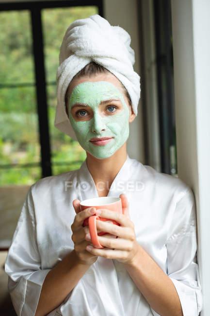 Retrato de mulher na máscara facial segurando caneca de café em casa — Fotografia de Stock