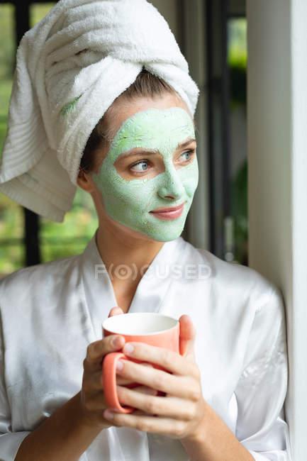 Frontansicht einer Frau mit Gesichtsmaske mit Kaffeebecher zu Hause — Stockfoto