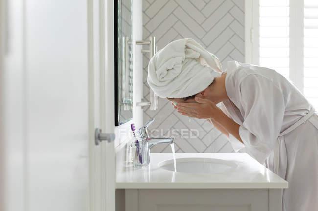 Vista lateral mulher lavando sua máscara facial na pia do banheiro em casa — Fotografia de Stock