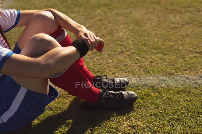 Parte centrale del giocatore di calcio femminile seduto al campo sportivo in una giornata di sole — Foto stock