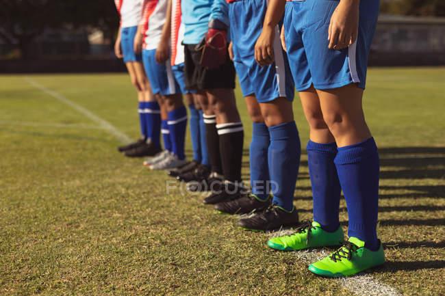 Seção média de jogador de futebol feminino em pé em fila no campo de esportes no dia ensolarado — Fotografia de Stock