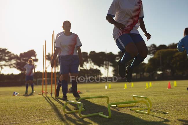 Vista de bajo ángulo de diversas jugadoras de fútbol femenino saltando sobre obstáculos durante el entrenamiento en el campo deportivo en un día soleado - foto de stock