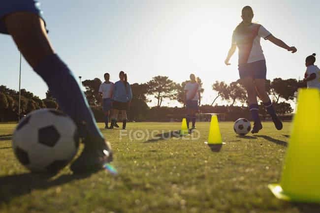 Vista a basso angolo di diverse giocatrici di calcio che passano la palla tra i coni durante l'allenamento sul campo — Foto stock