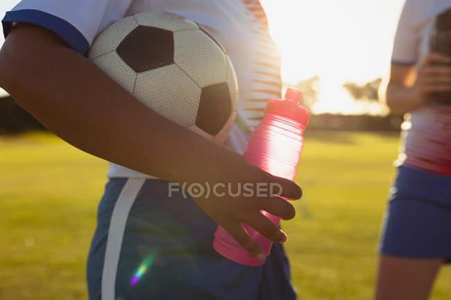 Metà sezione del giocatore di calcio femminile che tiene palla e bottiglia d'acqua sul campo — Foto stock