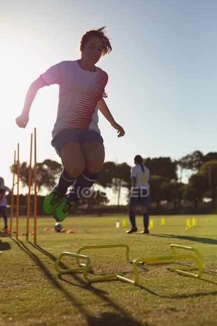 Vista de ángulo bajo de la jugadora de fútbol femenina caucásica saltando sobre obstáculos durante el entrenamiento en el campo deportivo - foto de stock