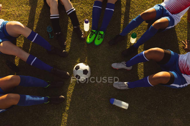 High angle view of female soccer players sitting in a circle with ball in between — Stock Photo