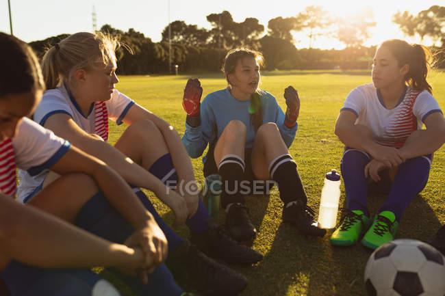 Vorderansicht von erschöpften Fußballerinnen, die auf dem Feld sitzen und sich auf dem Sportplatz unterhalten. — Stockfoto