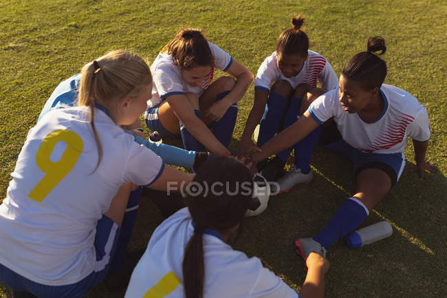 High angle view of happy diverse female soccer players forming a hand stack on the field on a sunny day — стоковое фото