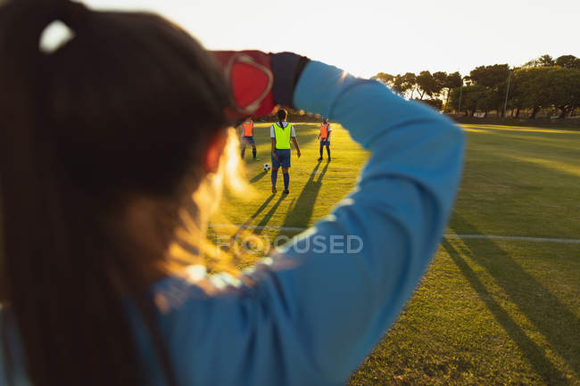 Rear view of Caucasian female goalkeeper in position to defend goal during competition at sport field. — Stockfoto