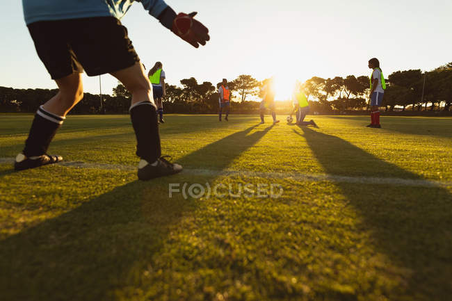 Rear view of Caucasian female goalkeeper defending goal during competition at sport field. — Stockfoto