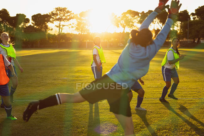 Rear view of Caucasian female goalkeeper defending goal during competition at sport field. — Stock Photo