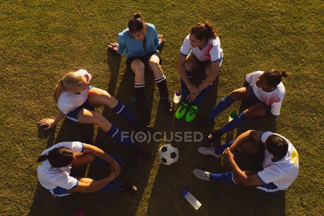 Високий кут зору вичерпали різні жінки футбольні гравці сидять у колі і розмовляли один з одним на полі — стокове фото