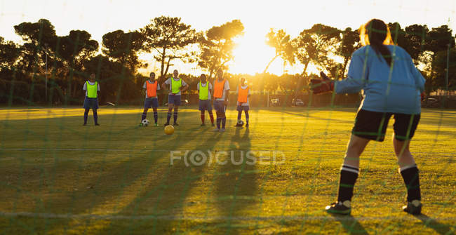 Rear view of Caucasian goalkeeper defending goal during competition at sport field. — Stock Photo
