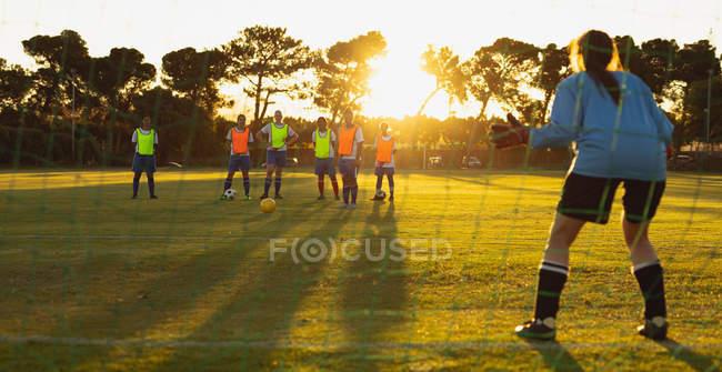 Vista retrovisora del portero caucásico defendiendo el gol durante la competición en el campo deportivo. - foto de stock