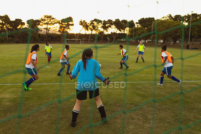 Rear view of determined diverse female soccer players playing at sports field — Stockfoto