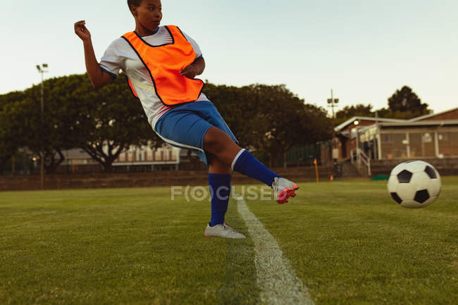 Side view of African-american female soccer player kicking ball from marking line at sports field — стокове фото