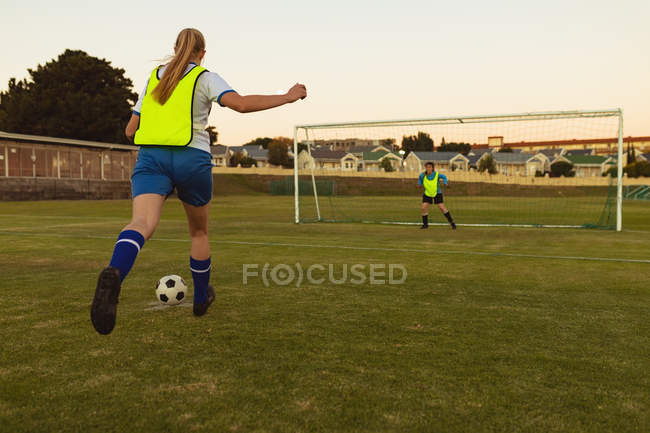 Rear view of determined Caucasian players playing soccer at sports field — Stockfoto
