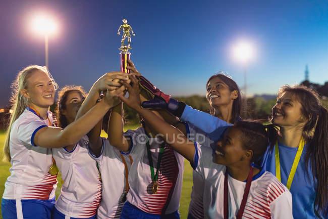 Vista frontal de la diversa selección de fútbol femenino sosteniendo trofeo después de ganar el juego en el campo deportivo - foto de stock