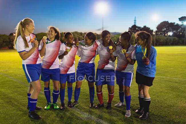 Front view of diverse female soccer team showing medal to each other at sports field — Stockfoto