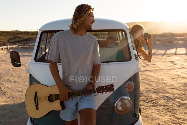 Opinião dianteira o homem caucasiano novo com a guitarra que olha a mulher que toma o retrato com a câmera digital fora do indicador da camionete de campista — Fotografia de Stock