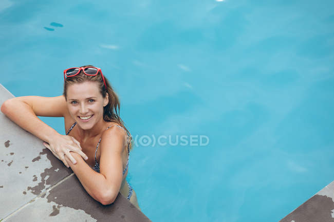 Portrait of happy Caucasian woman standing at the edge of swimming pool — Stock Photo