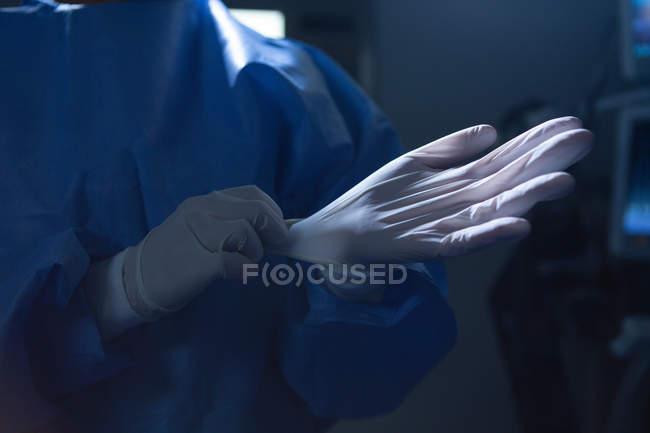 Sezione media di chirurgo donna con guanti chirurgici in sala operatoria in ospedale — Foto stock