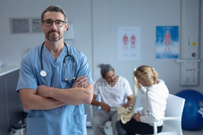 Вид з Кавказького чоловічого хірурга з рука перетнув і стетоскоп навколо шиї дивлячись на камеру в лікарні — стокове фото