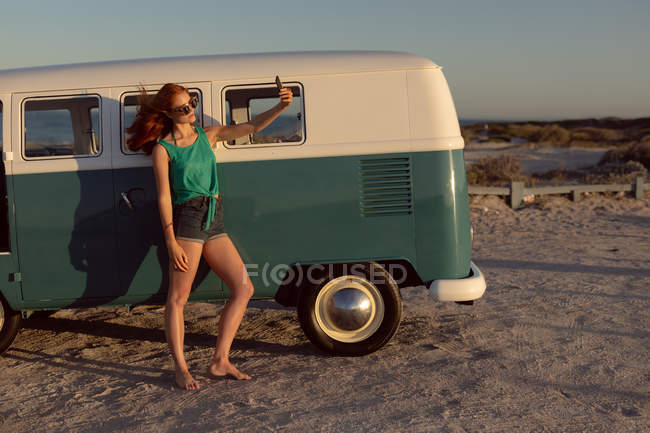 Front view of beautiful young Caucasian woman with sunglasses taking selfie near camper van at beach — Stock Photo