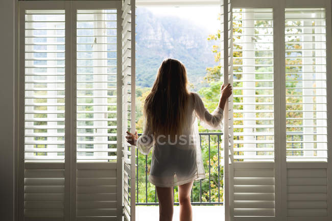 Rear view of Caucasian woman standing by door at home — Stock Photo
