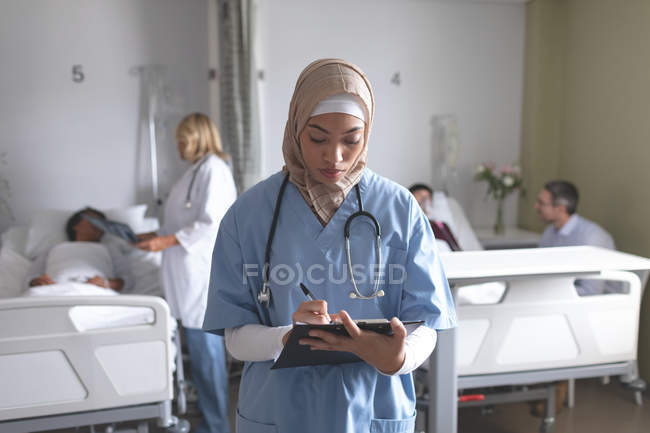 Front view of mixed race female doctor in hijab writing on clipboard in the ward at hospital. In the background diverse doctors are interacting with their patients. — Stock Photo