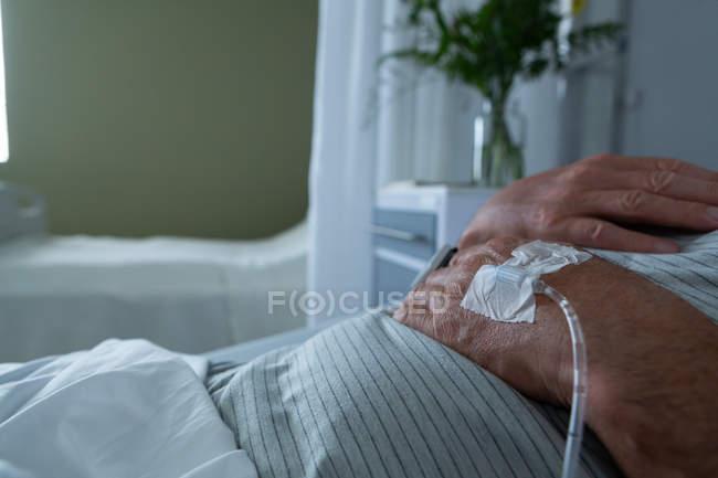 Sección media del paciente masculino acostado en la cama con las manos sobre el pecho en la sala del hospital. Está recibiendo terapia intravenosa. . - foto de stock