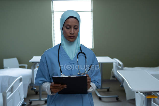 Front view of mixed race female doctor in hijab writing in clipboard in the ward in hospital — Stock Photo