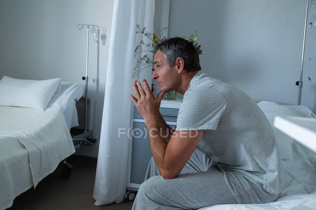Side view of thoughtful Caucasian male patient sitting on bed with elbows on the knee in the ward in hospital — Stock Photo