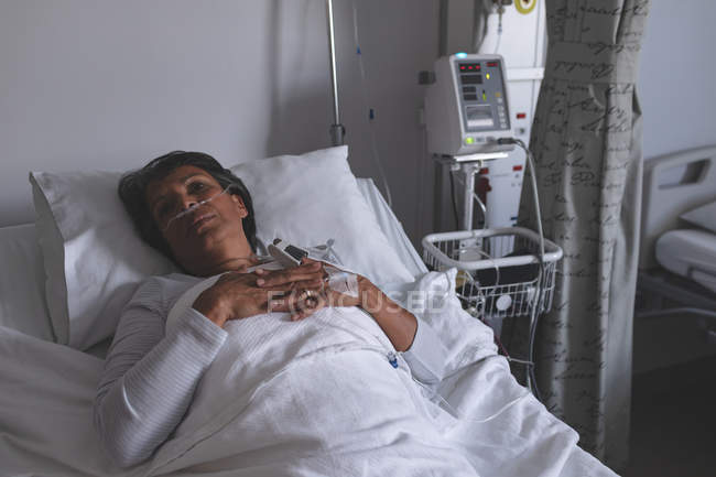 High angle view of thoughtful mixed race female patient relaxing in bed in the ward at hospital. Woman is keeping her hands on chest. — Stock Photo