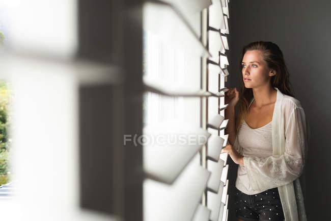 Вид спереди вдумчивой кавказской женщины, смотряй через окно вслепую дома — стоковое фото