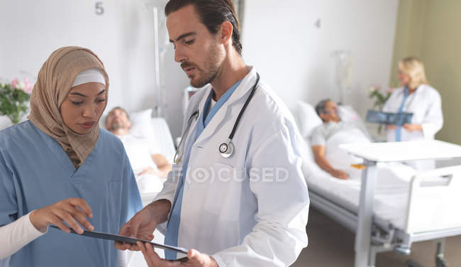 Side view of diverse doctors discussing over clipboard in the ward at hospital. In the background Caucasian female doctor discusses x-ray with senior mixed-race patient. — Stock Photo