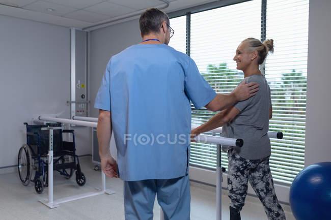 Задний план кавказского физиотерапевта, помогающего пациенту ходить с параллельными решетками в больнице — стоковое фото