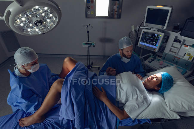 High angle view of Caucasian female surgeon examining pregnant woman during delivery while man holding her hand in operating room at hospital — Stock Photo