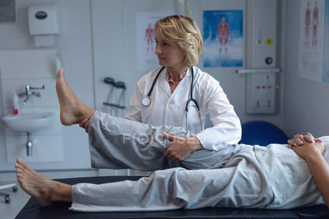 Opinião lateral o paciente masculino de exame do doutor fêmea caucasiano para trás no hospital — Fotografia de Stock