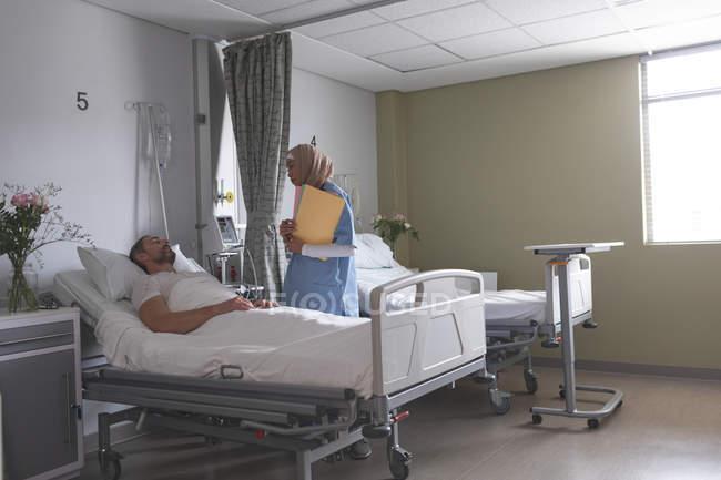 Seitenansicht der gemischten Rasse Ärztin interagiert mit kaukasischen männlichen Patienten auf der Station im Krankenhaus — Stockfoto