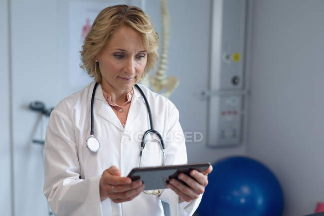 Front view of Caucasian female doctor with stethoscope around her neck using digital tablet in the hospital — Stock Photo