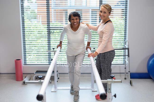 Физиотерапевт-кавказка помогает пациентке ходить с параллельными решетками в больнице — стоковое фото