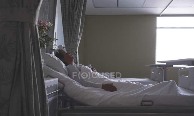Seitenansicht einer reiferen Patientin mit gemischter Rasse, die auf der Station im Krankenhaus im Bett schläft — Stockfoto