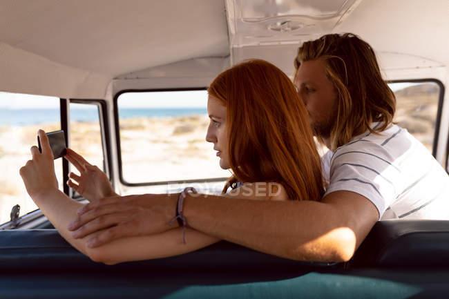 Вид сбоку на молодую кавказскую пару, делающую селфи с мобильным телефоном на переднем сиденье фургона на пляже — стоковое фото