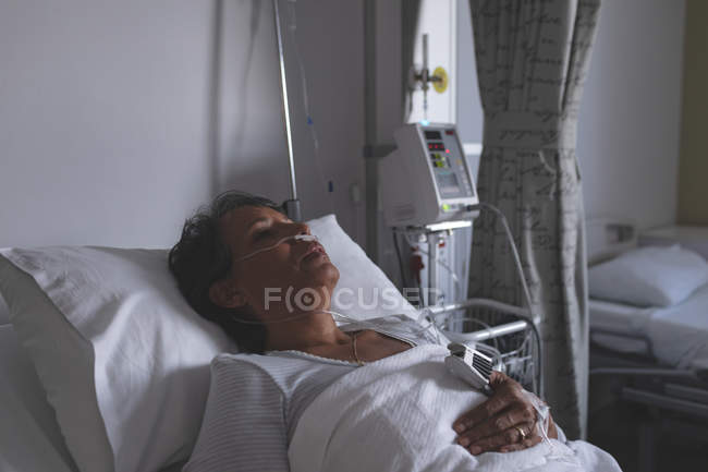 Portrait of mature mixed-race female patient sleeping in bed in the ward at hospital — Stock Photo