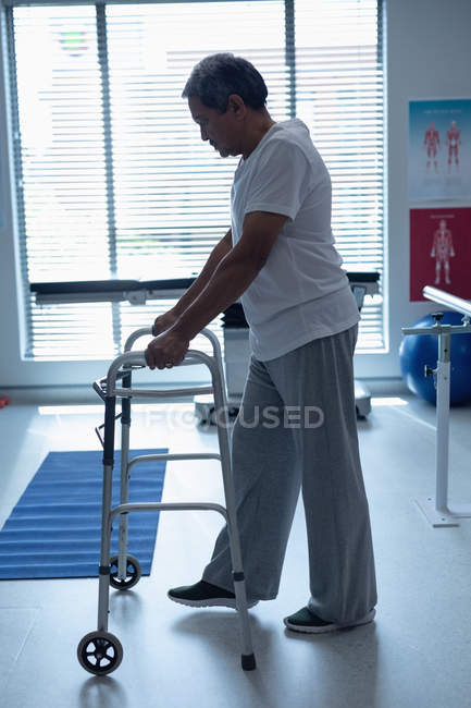 Side view of mixed race male patient walking with walker in the ward at hospital — Stock Photo