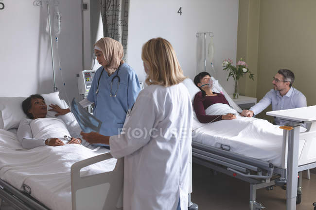 Side view of diverse female doctors interacting with female patient  in the ward at hospital. In the background Caucasian man is holding the hand of Asian woman who is lying in bed at hospital. — Stock Photo